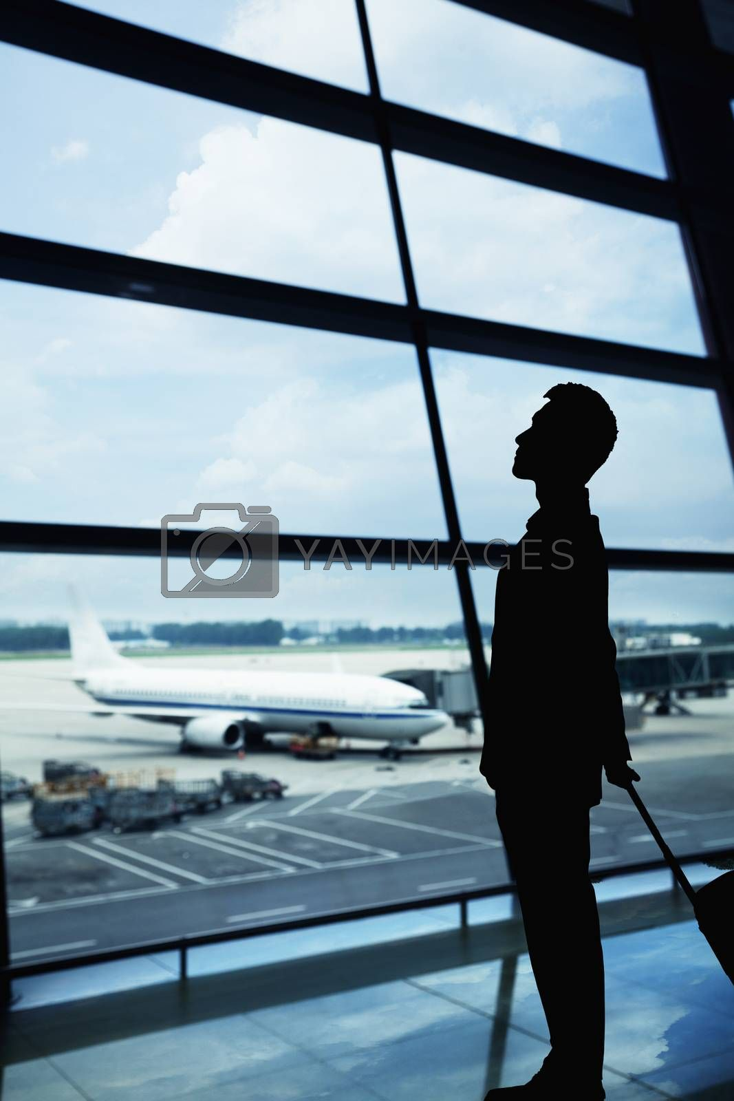 Silhouette of businessman waiting in the airport and looking out the window