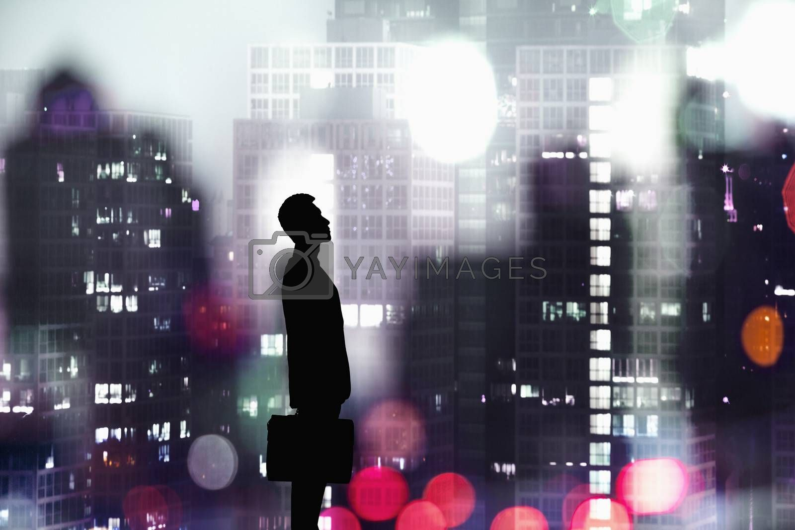 Silhouette of businessman holding a briefcase with a city at night time in the background