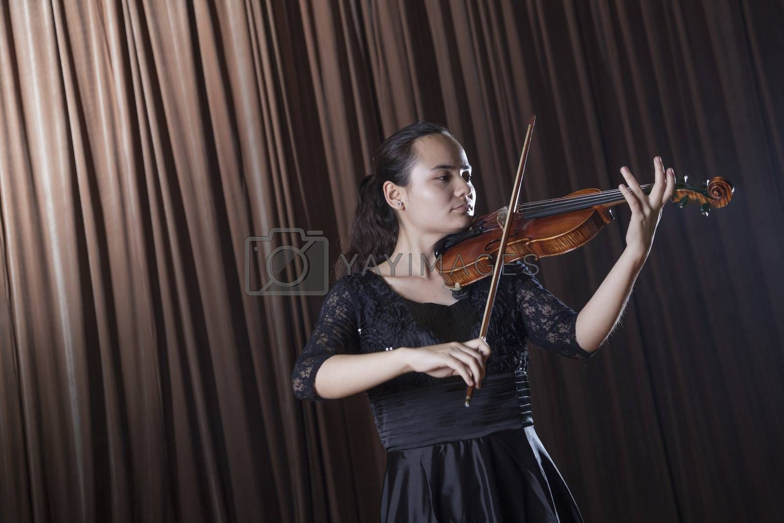 Violinist standing and playing the violin at a performance