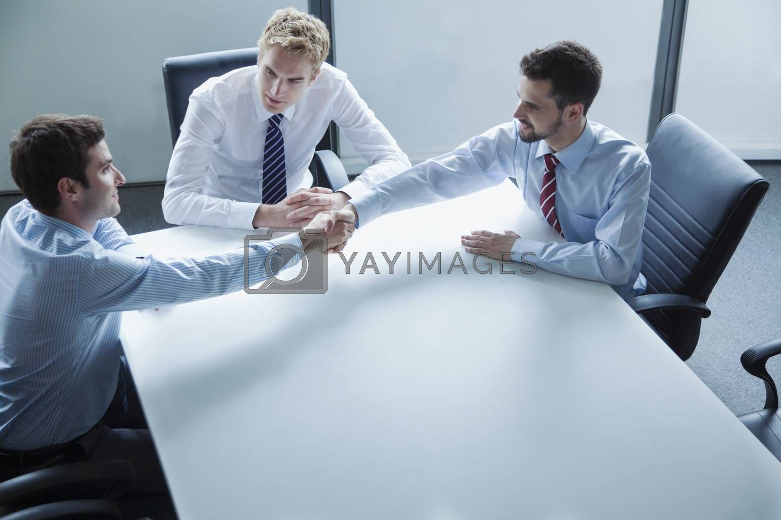 Businessmen shaking hands over the table in the office