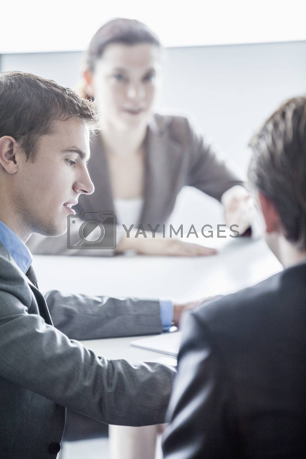 Three business people sitting at a table and having a business meeting in the office