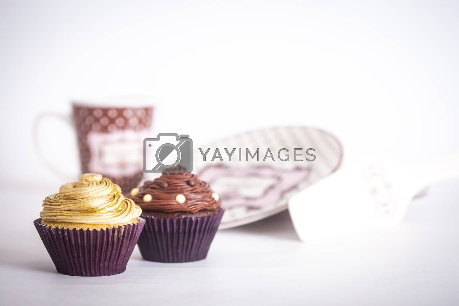 Cupcakes in front of plates and a mug, on a white background.