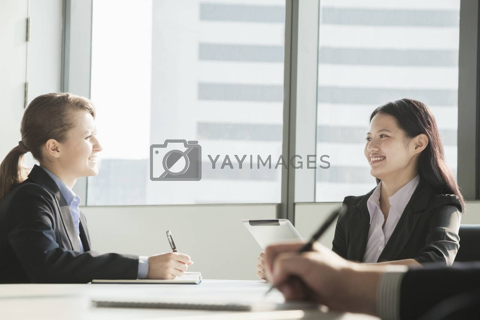 Two businesswomen smiling and looking at each other during a business meeting