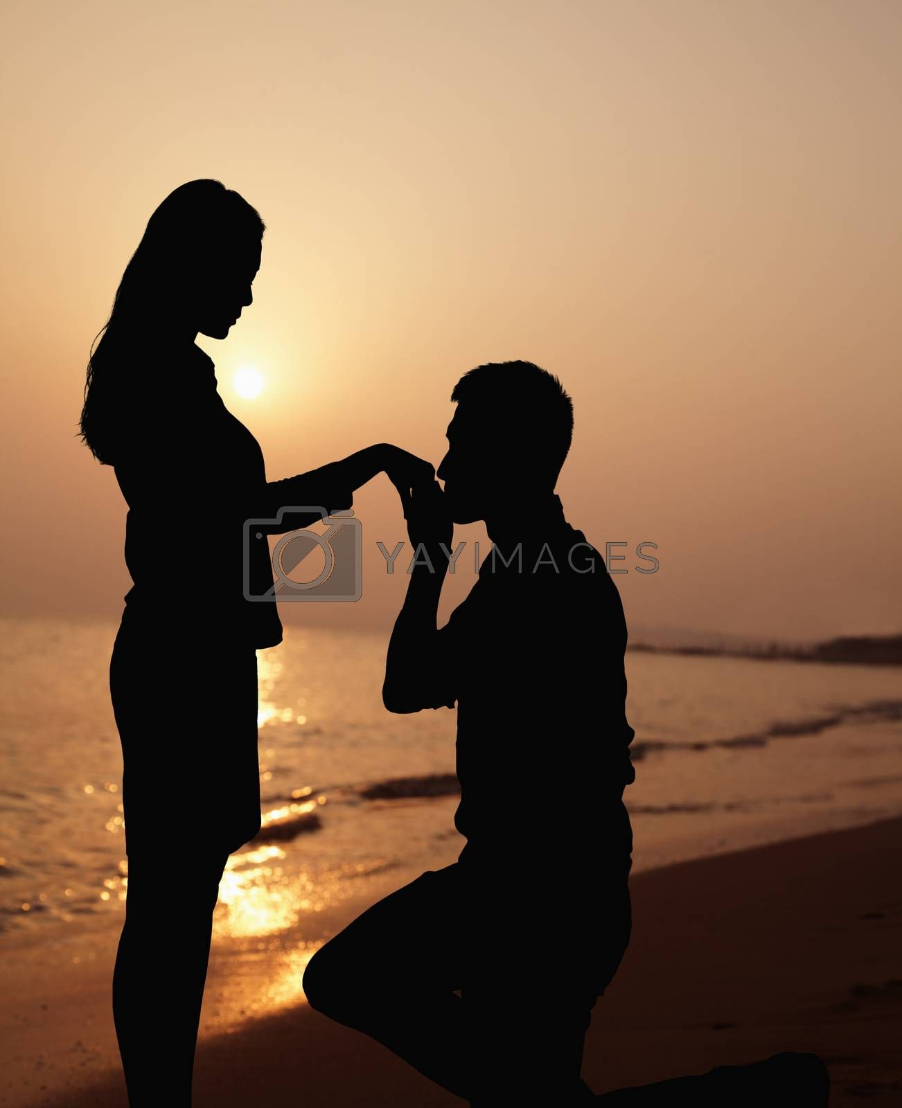 Silhouette of boyfriend kneeling and kissing his girlfriends hand on the beach at sunset by XiXinXing