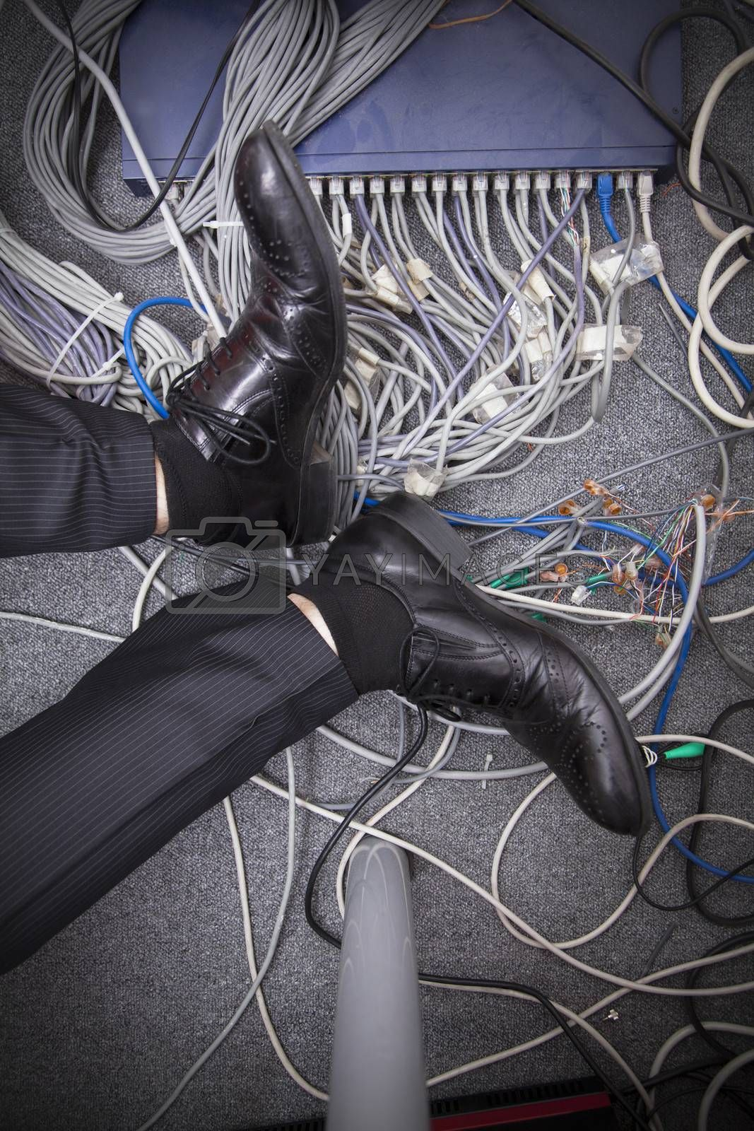 Businessman's feet on the ground surrounded by computer cables