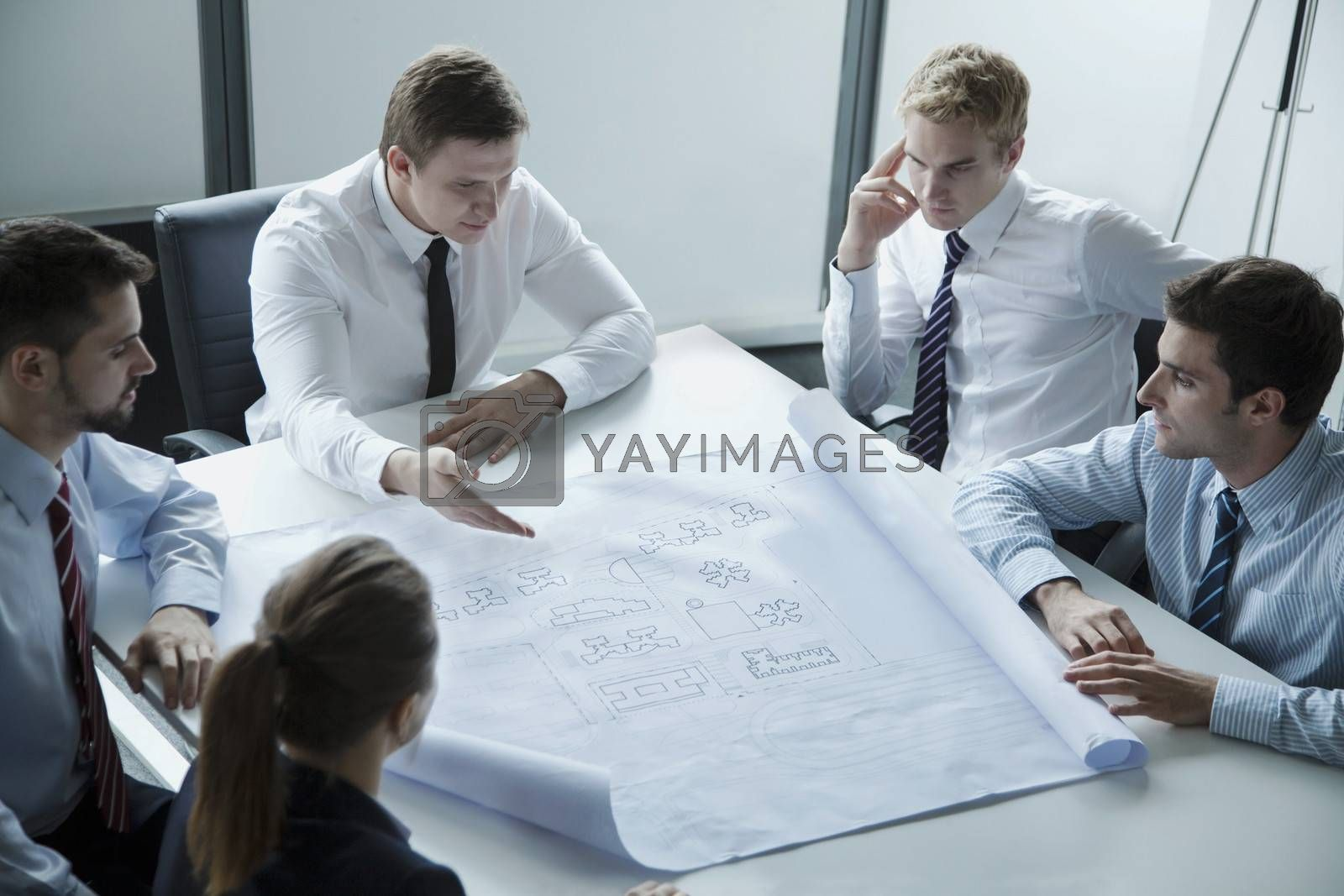 Five architects discussing and planning over a blueprint in the office