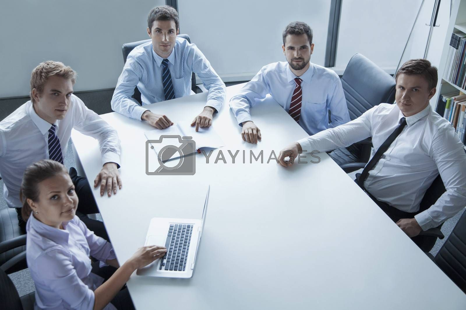 Five business people having a business meeting at the table in the office, looking at camera