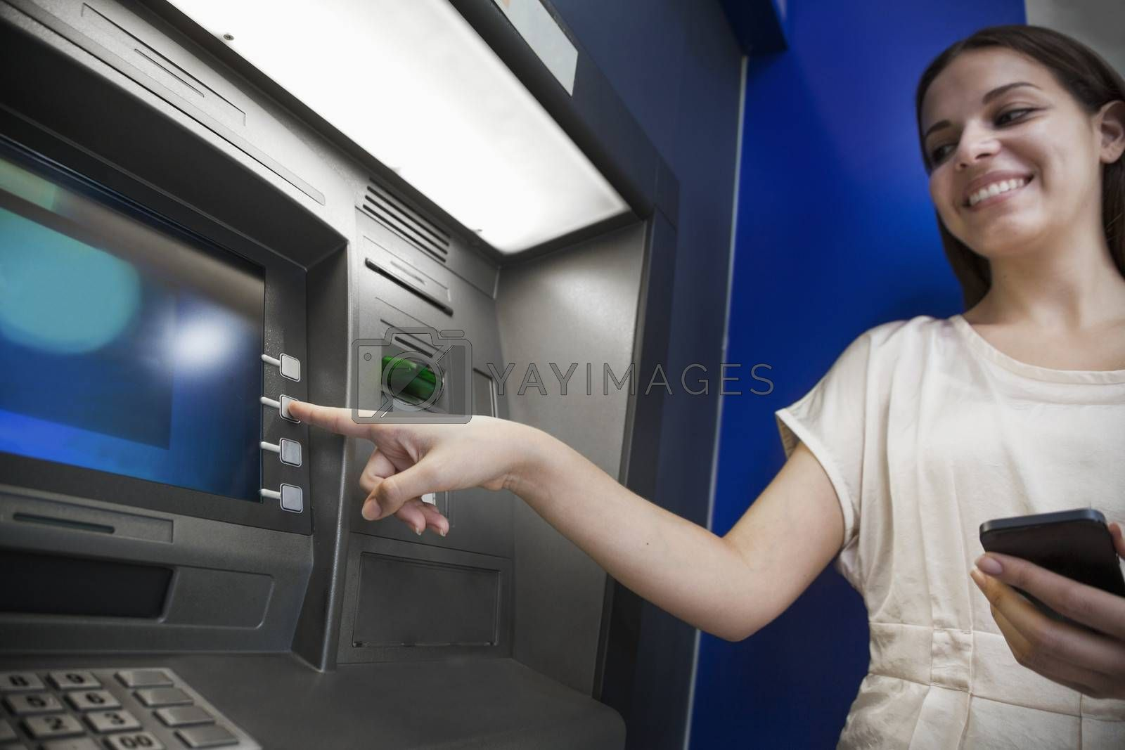 Smiling young woman withdrawing money from the ATM by XiXinXing