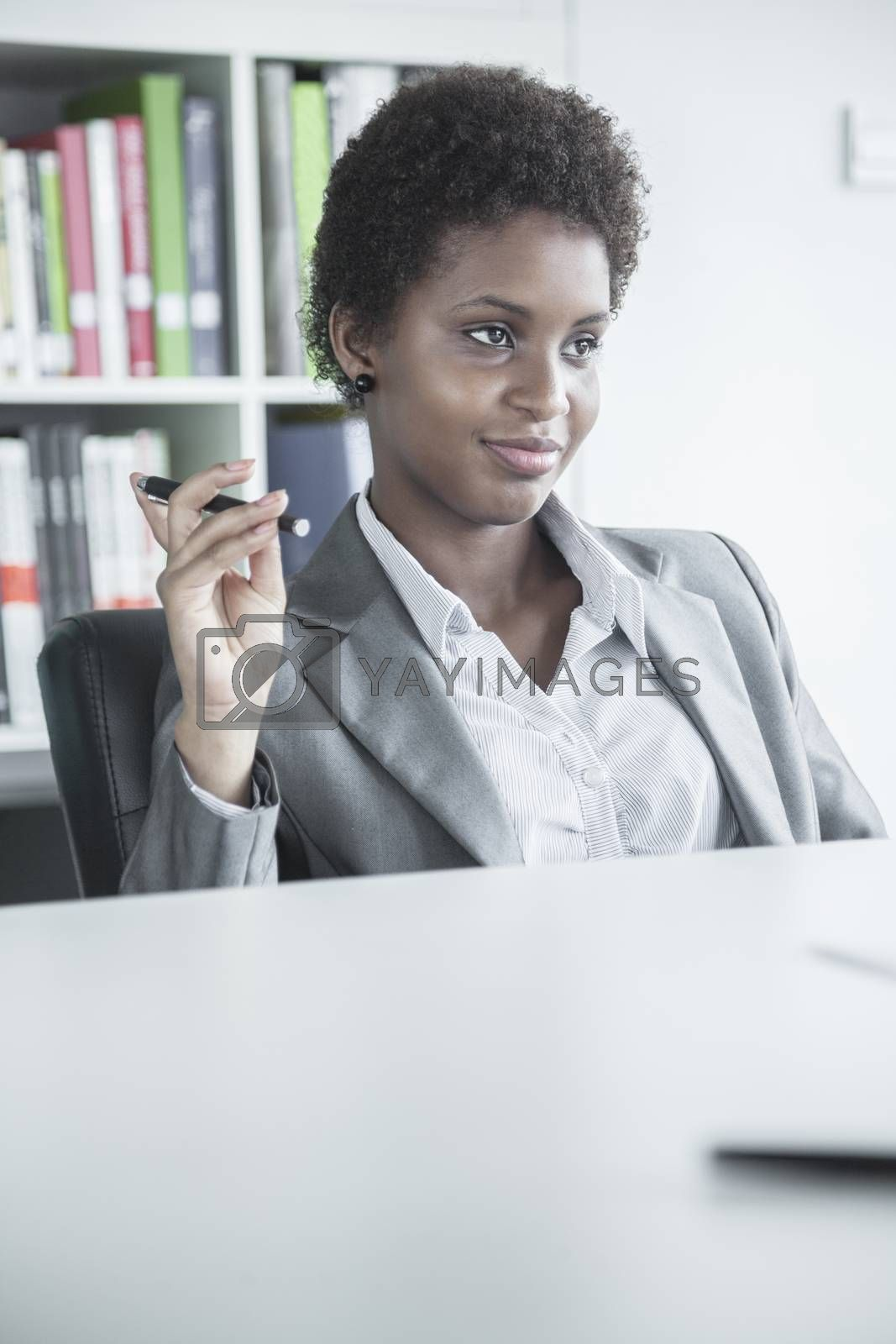 Portrait of young smiling businesswoman sitting at a table and holding a pen