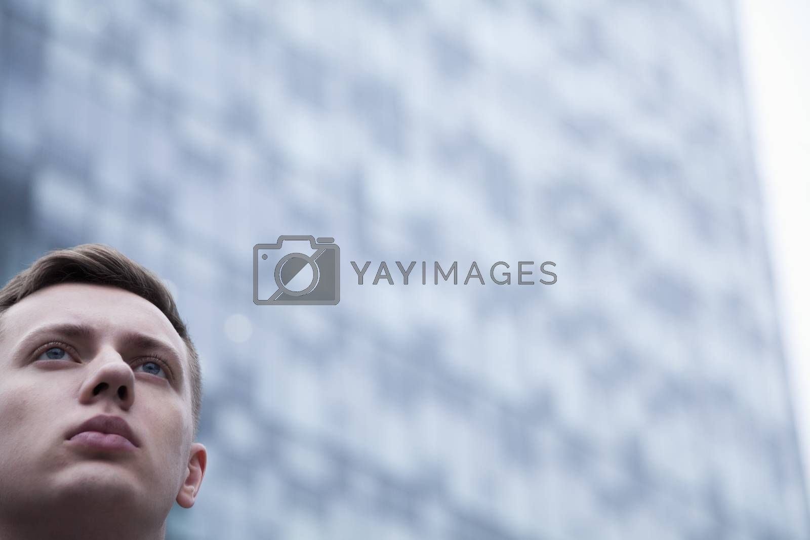 Portrait of serious young businessman looking up, outdoors, business district