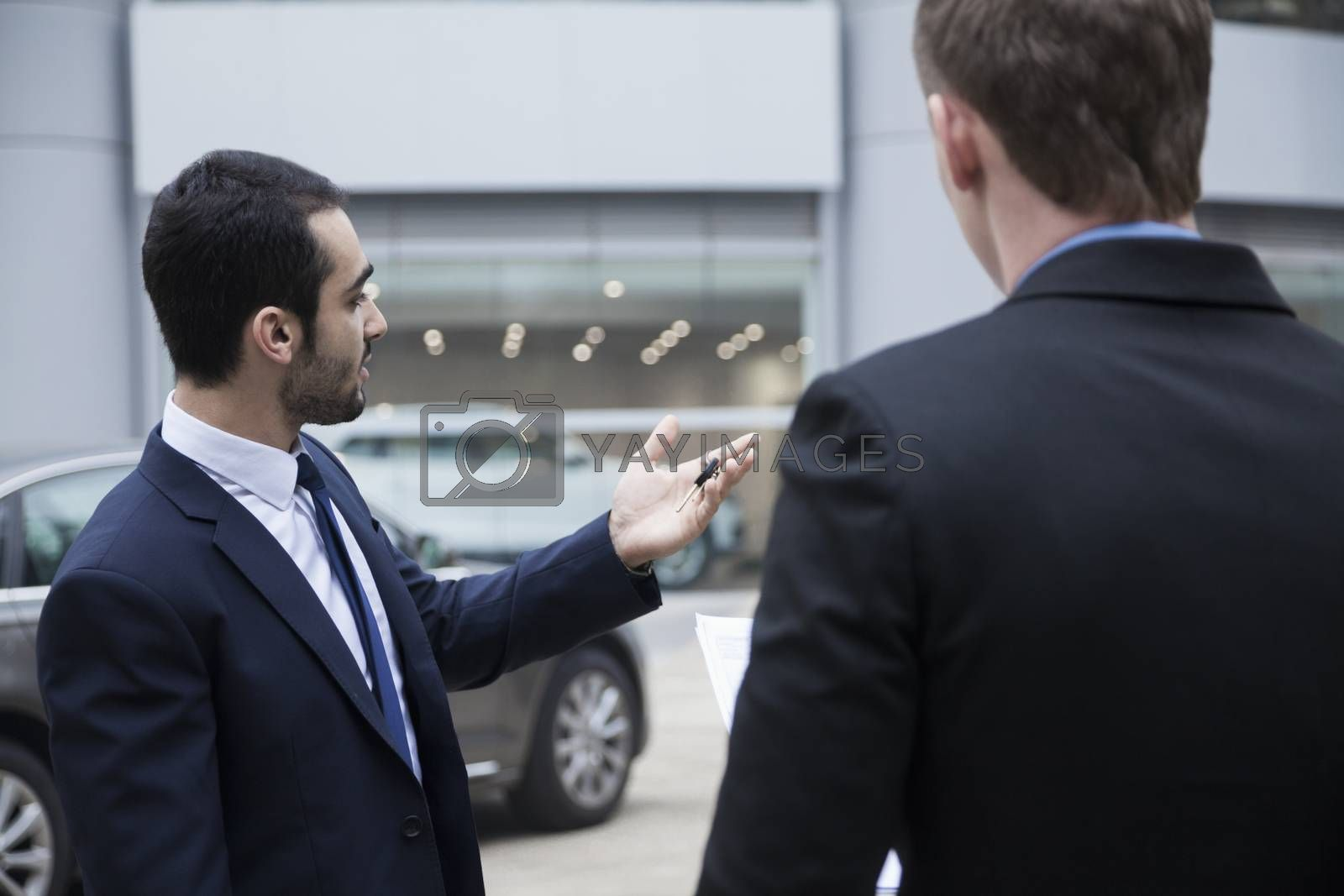 Car salesman holding car keys and selling a car to a young businessman by XiXinXing