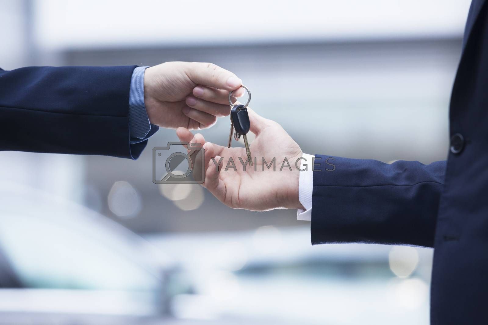 Car salesman handing over the keys for a new car to a young businessman, close-up  by XiXinXing