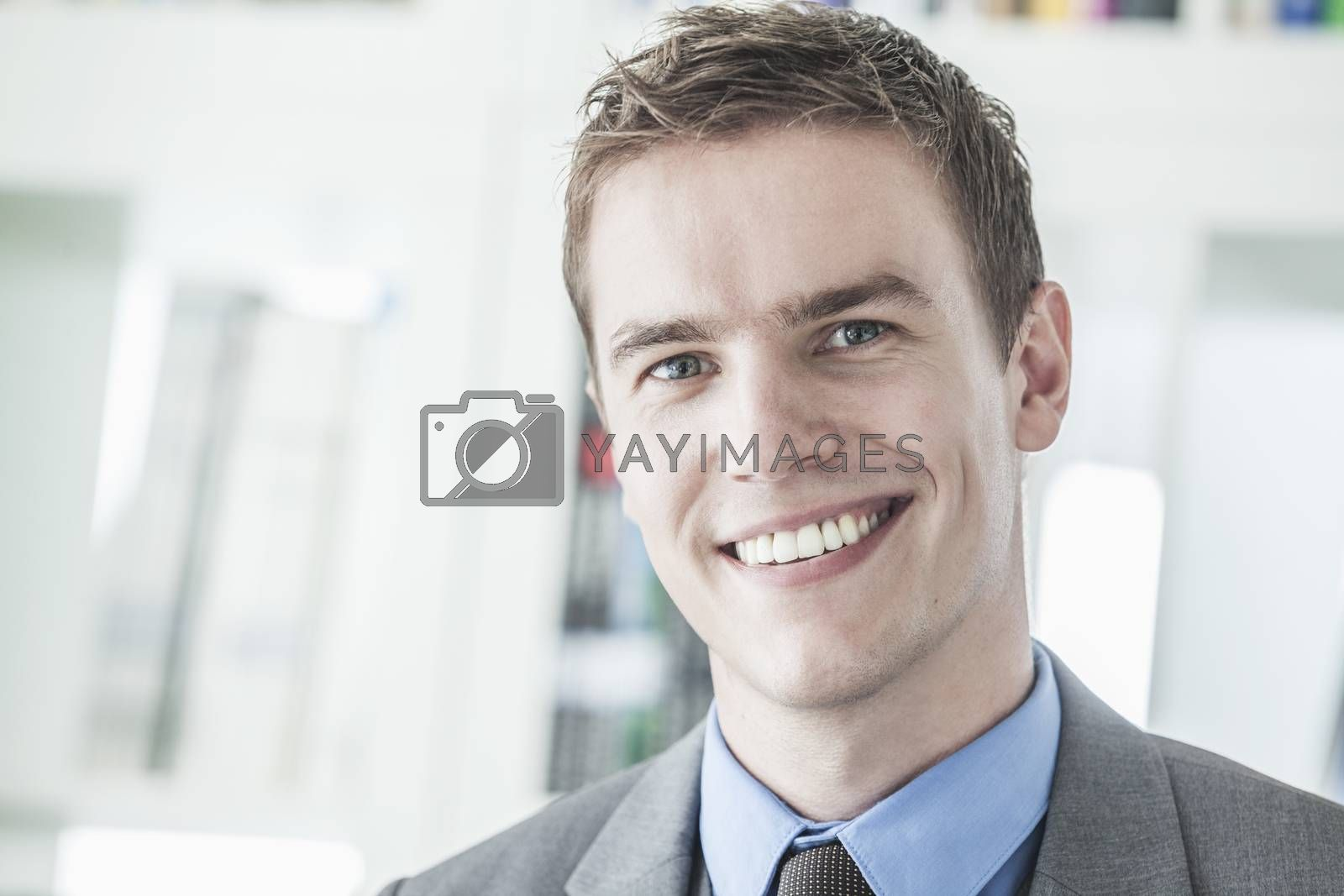 Portrait of young smiling businessman looking at camera, head and shoulders