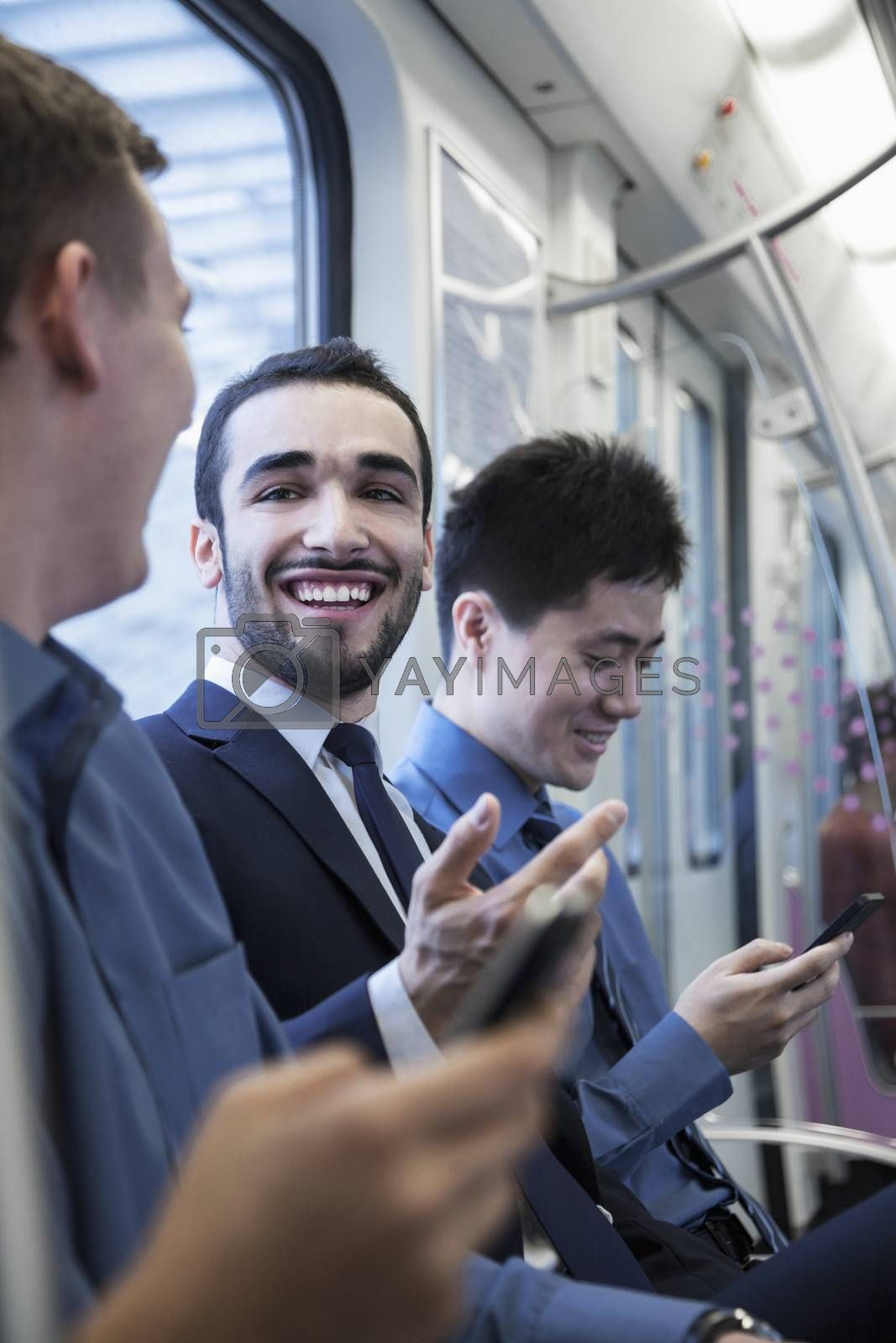 Three businessmen sitting in a row and talking on the subway