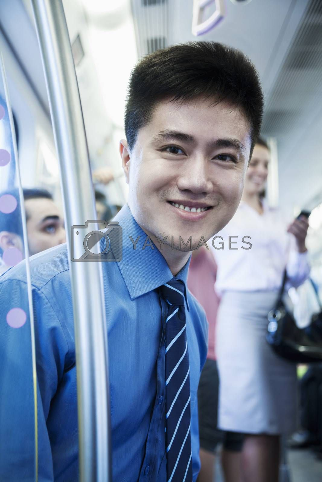 Portrait of young businessman sitting on the subway and looking at the camera