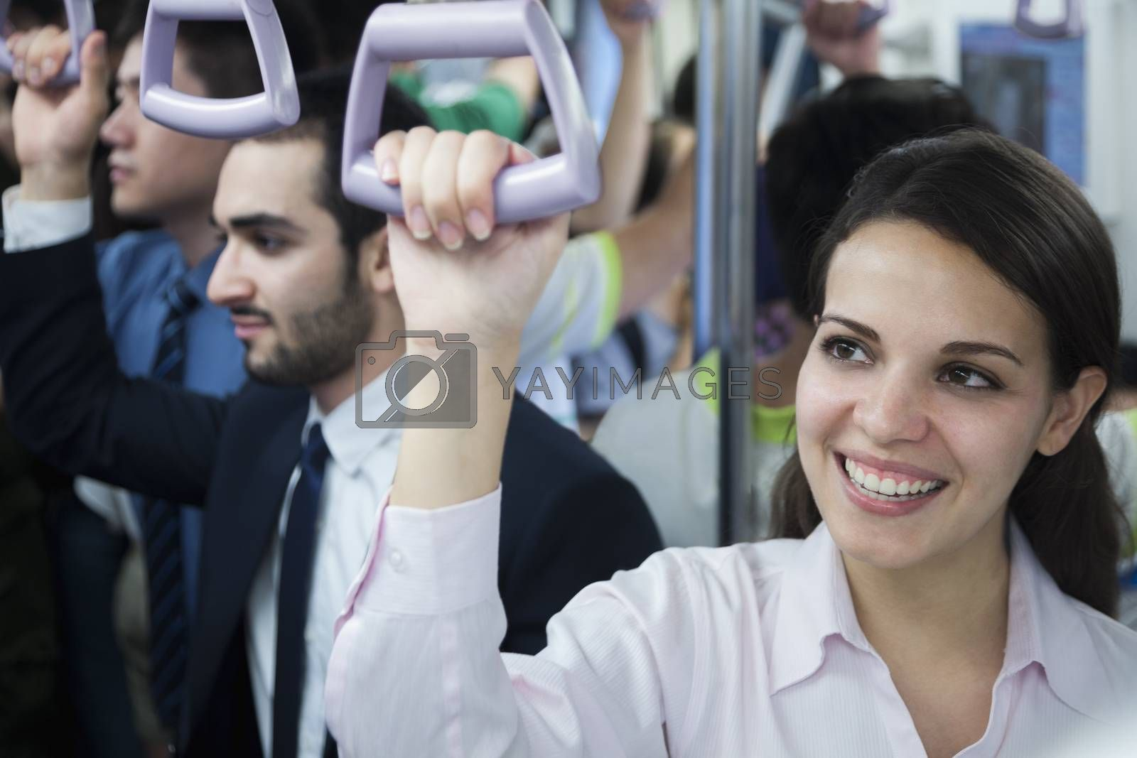 Portrait of smiling young businesswoman standing on the subway, looking away  by XiXinXing