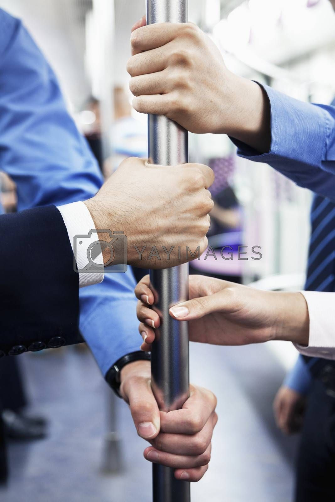 Close-up of four business people's hands holding the pole on the subway