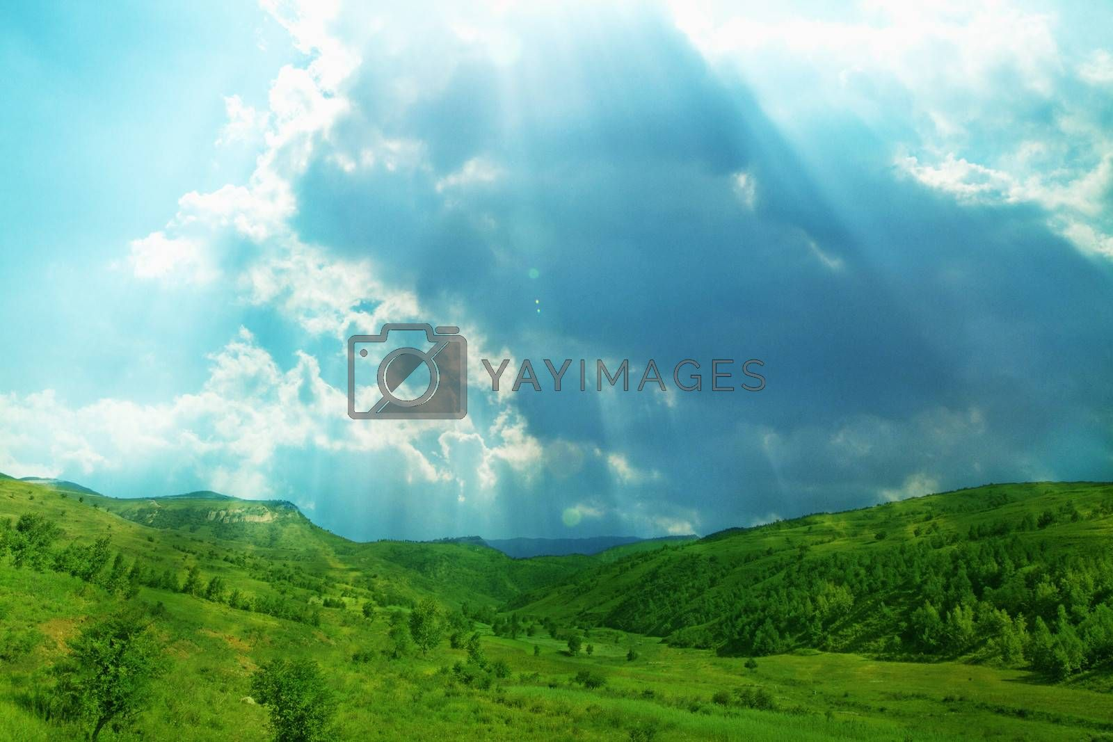 Lush, green landscape with sun shining through clouds.