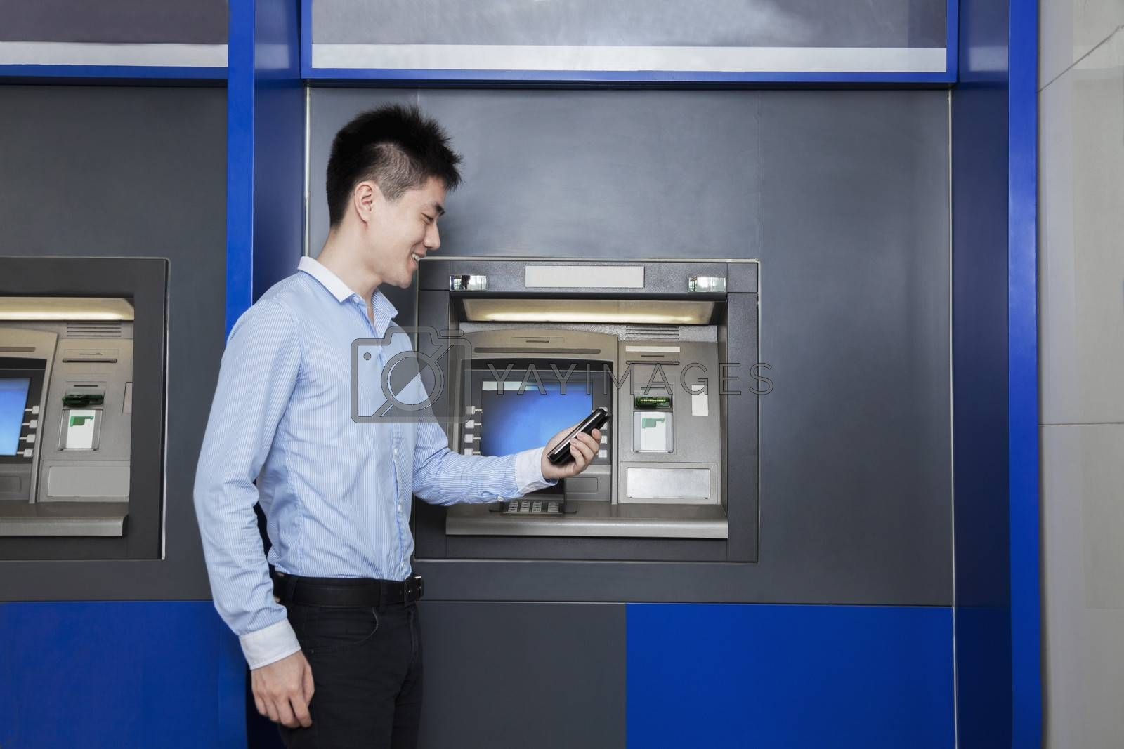 Smiling young businessman standing in front of an ATM and looking at his phone by XiXinXing