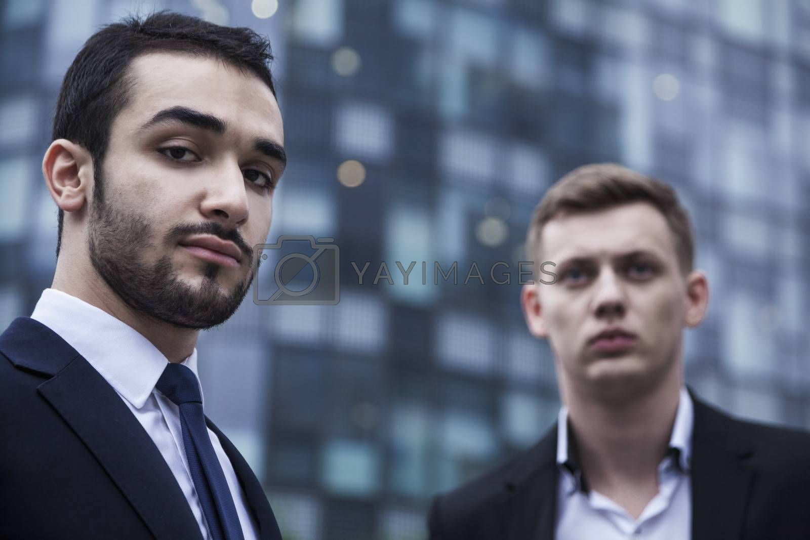Portrait of two serious young businessmen looking at the camera, outdoors, business district