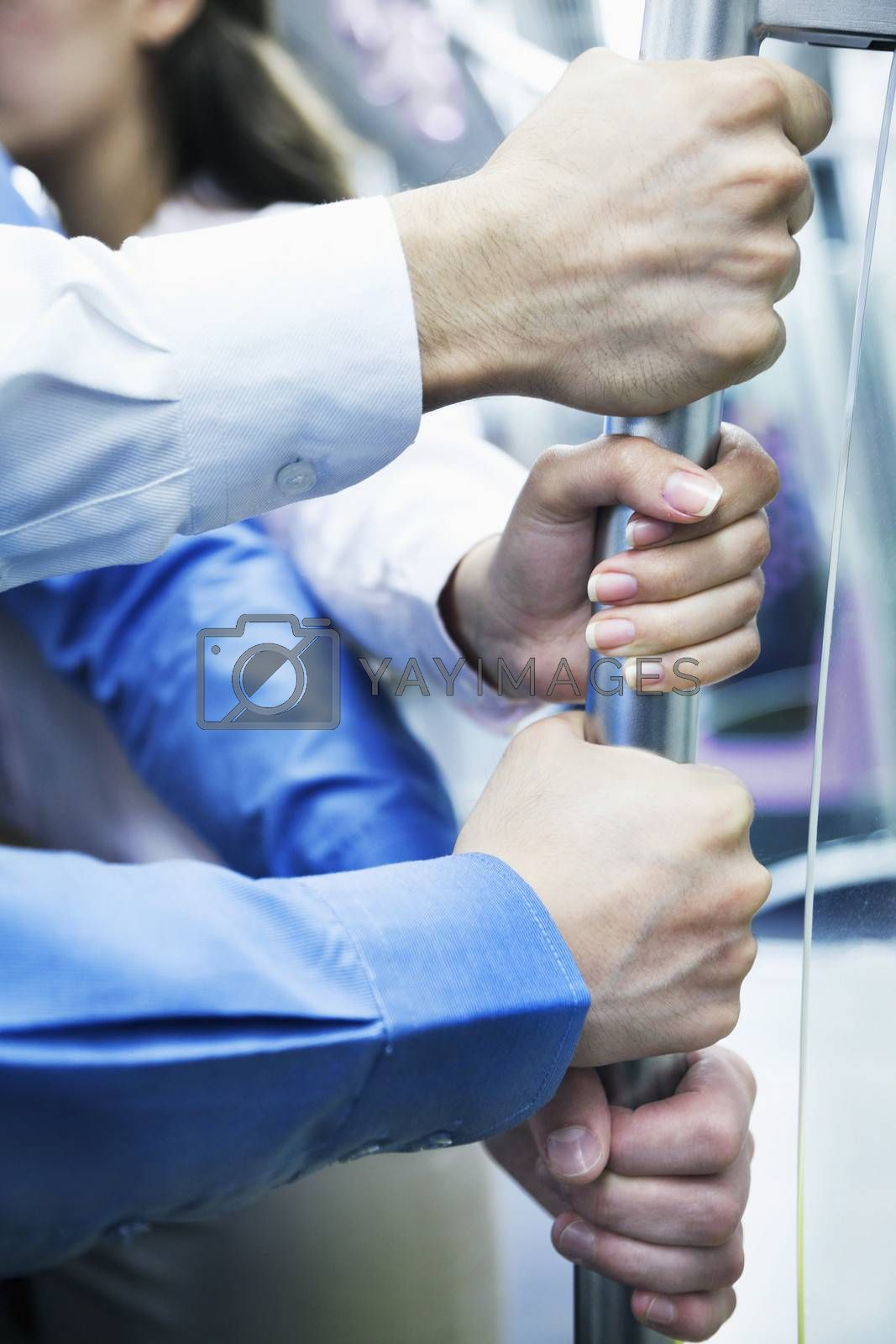 Close-up of four business people's hands holding the pole on the subway by XiXinXing