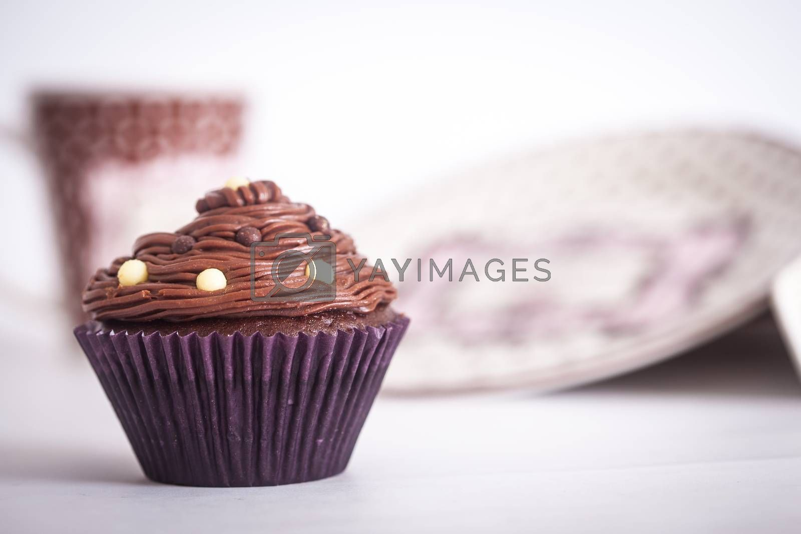 A cupcake in front of plates and a mug, on a white background.