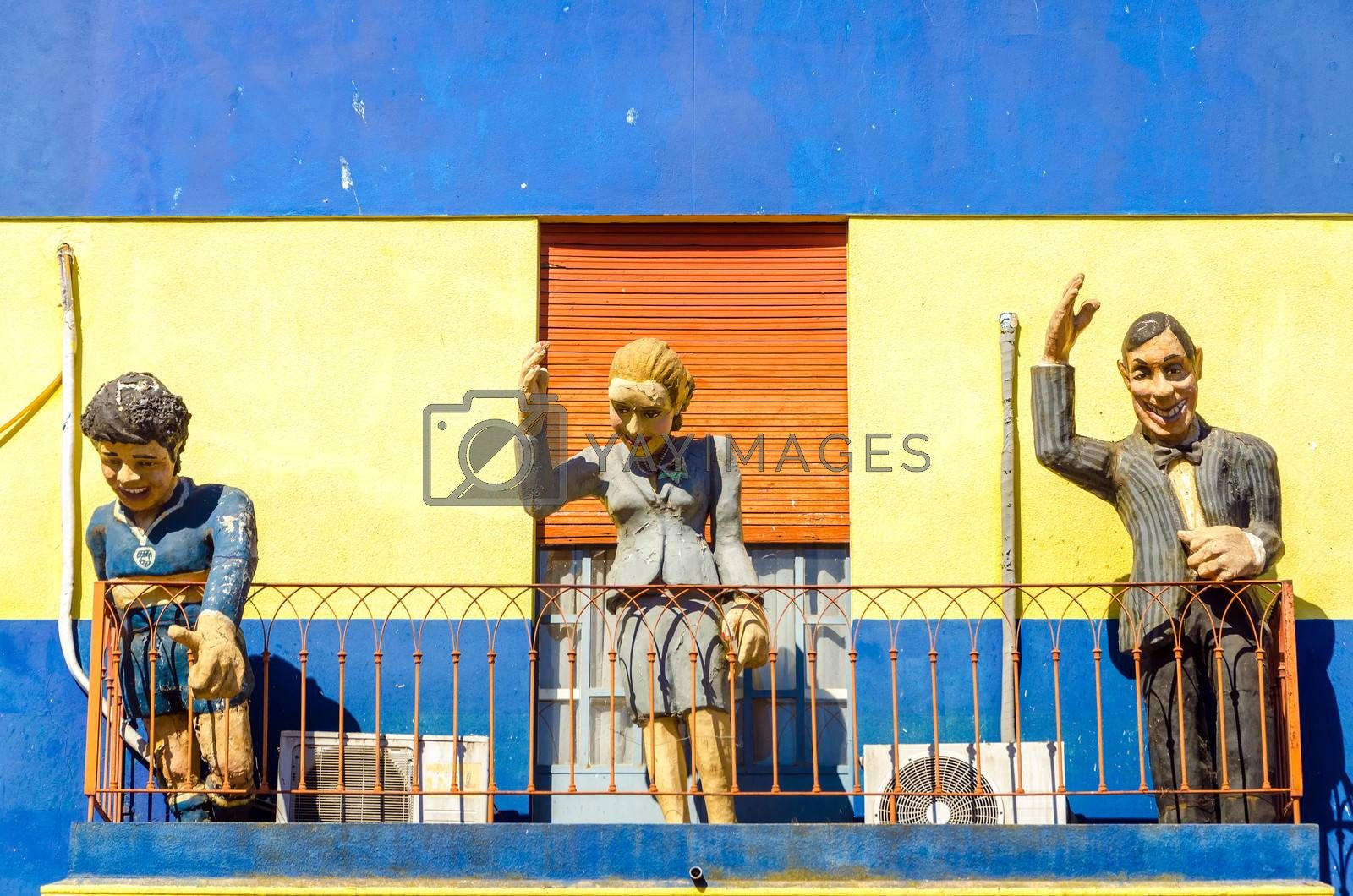 Statues with a yellow and blue wall in La Boca neighborhood of Buenos Aires, Argentina