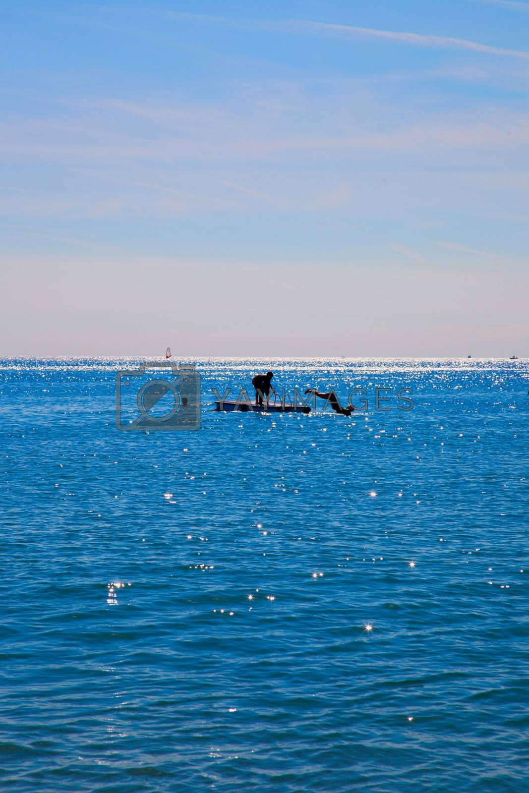 Unrecognizable people diving from a platform in the sea