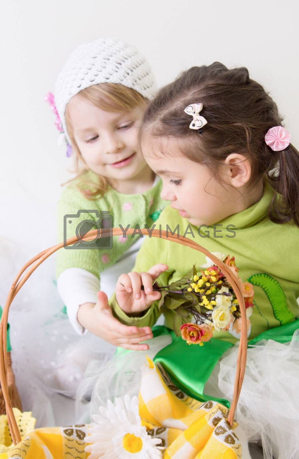 Two cute girls with basket and flowrs playing