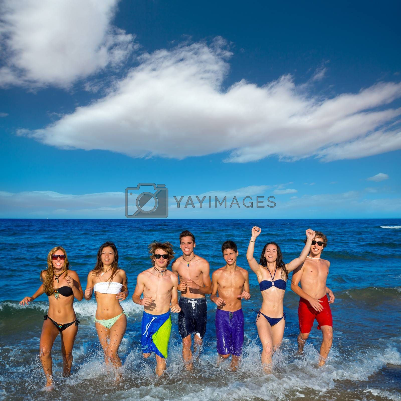 Teenagers group running happy splashing on the beach in summer vacations