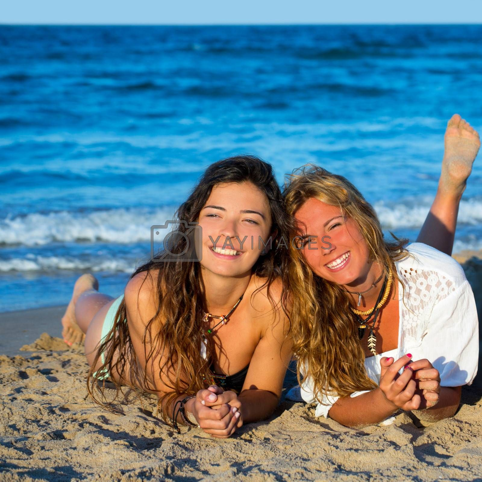 Girls friends having fun happy lying on the beach sand shore