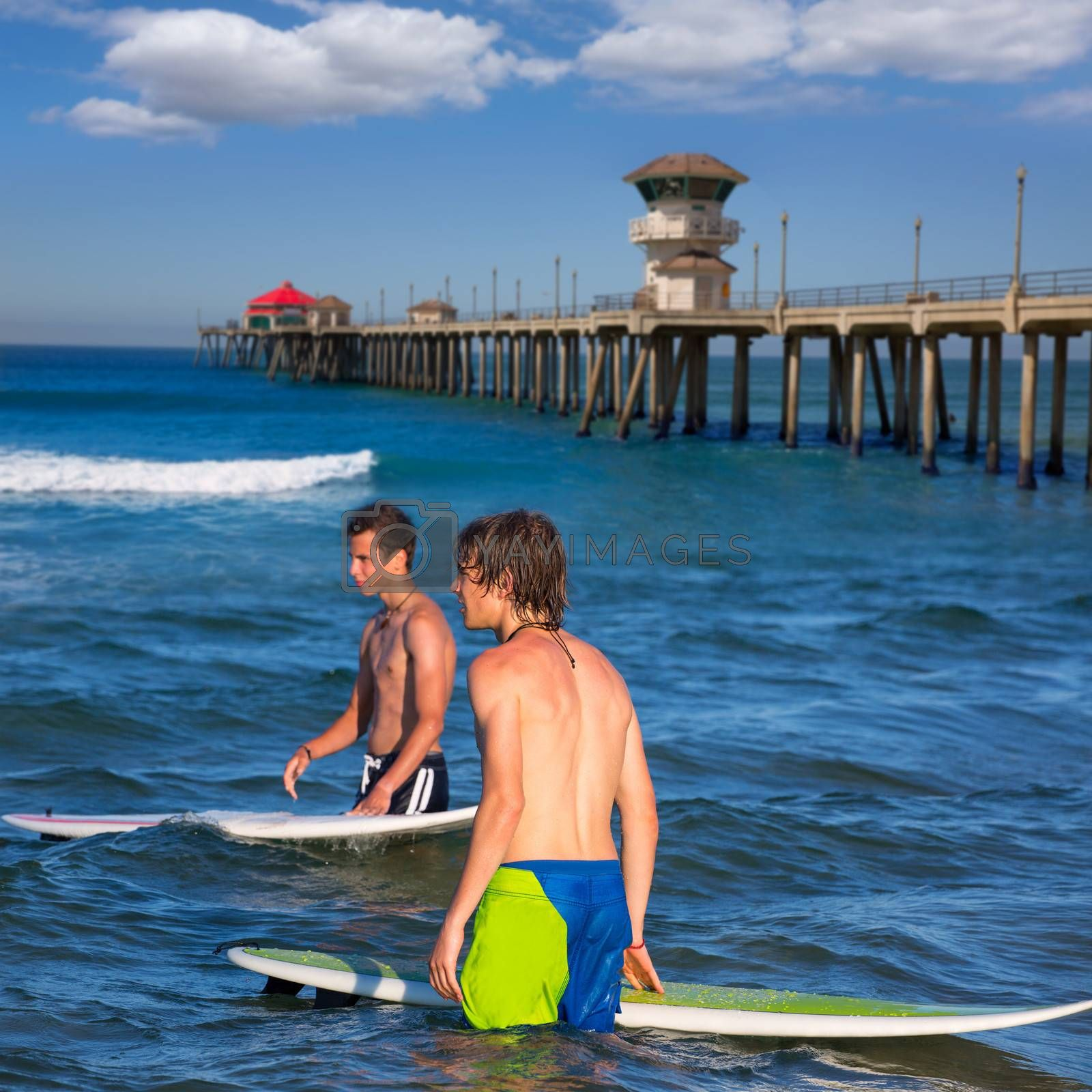 surfers waiting for the waves on Huntington beach pier California