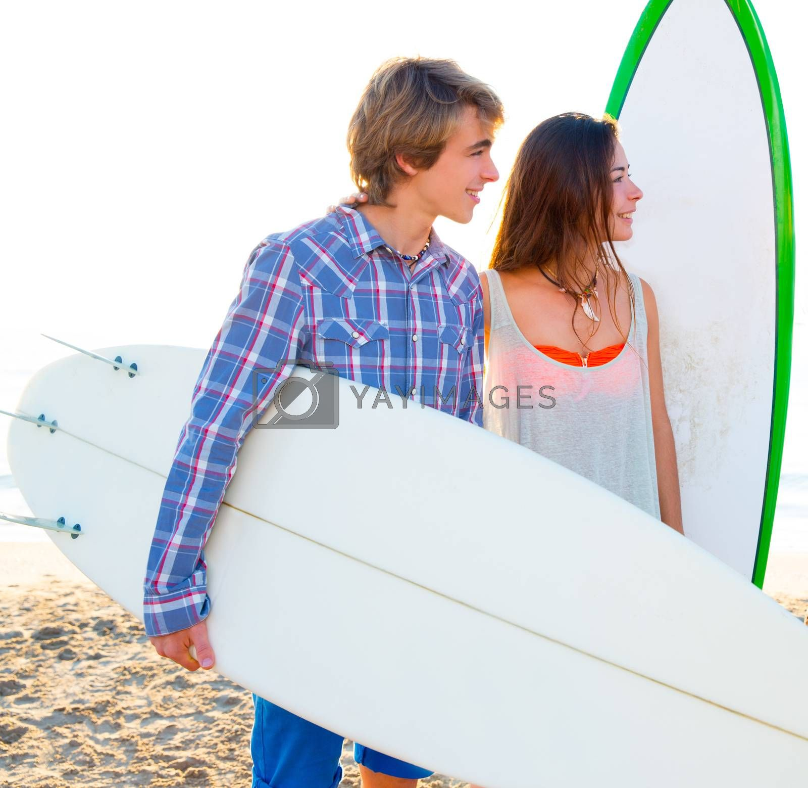 Teen surfer couple on beach shore with surfboards high key