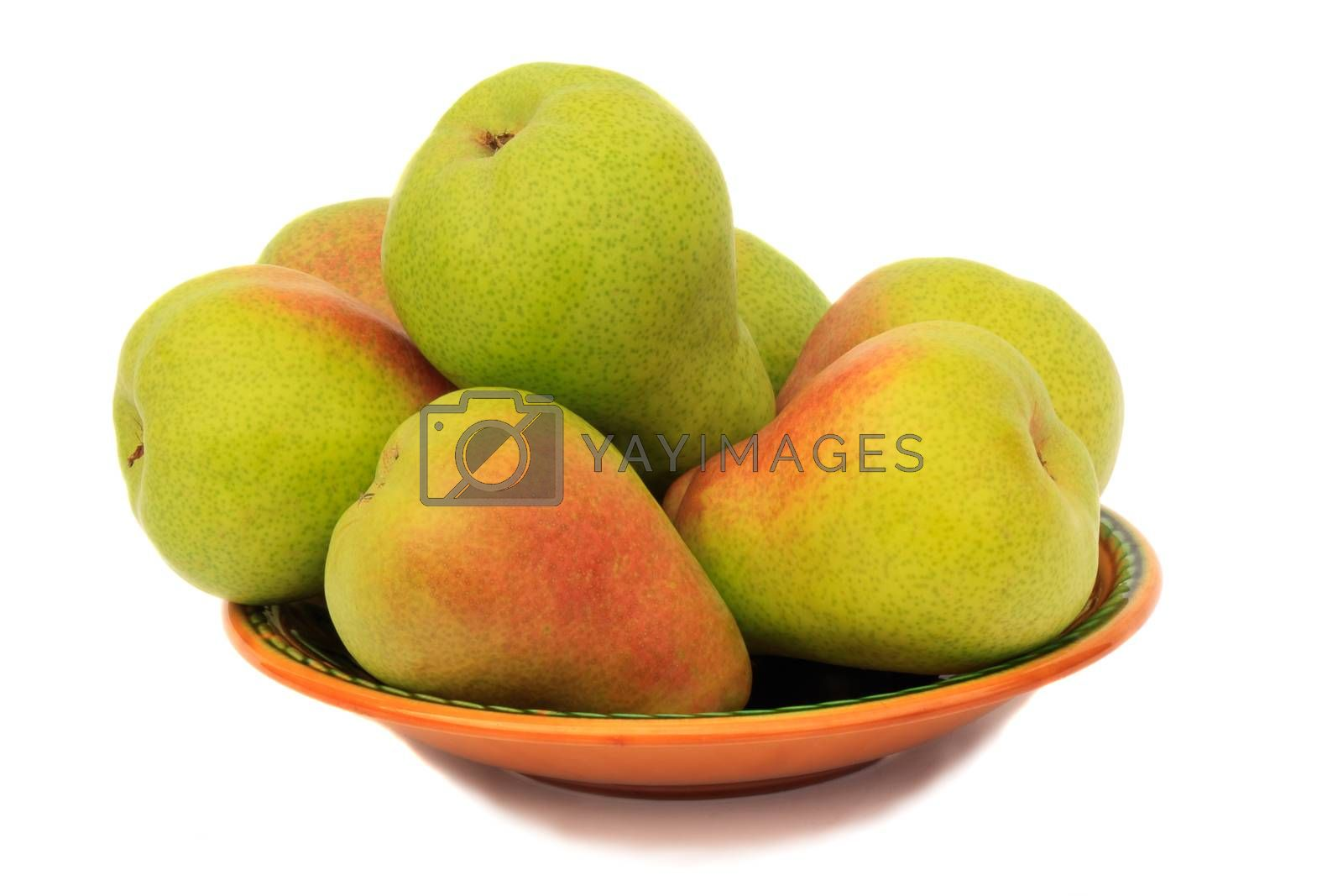 Large ripe yellow pears on a ceramic plate. Presented on a white background.