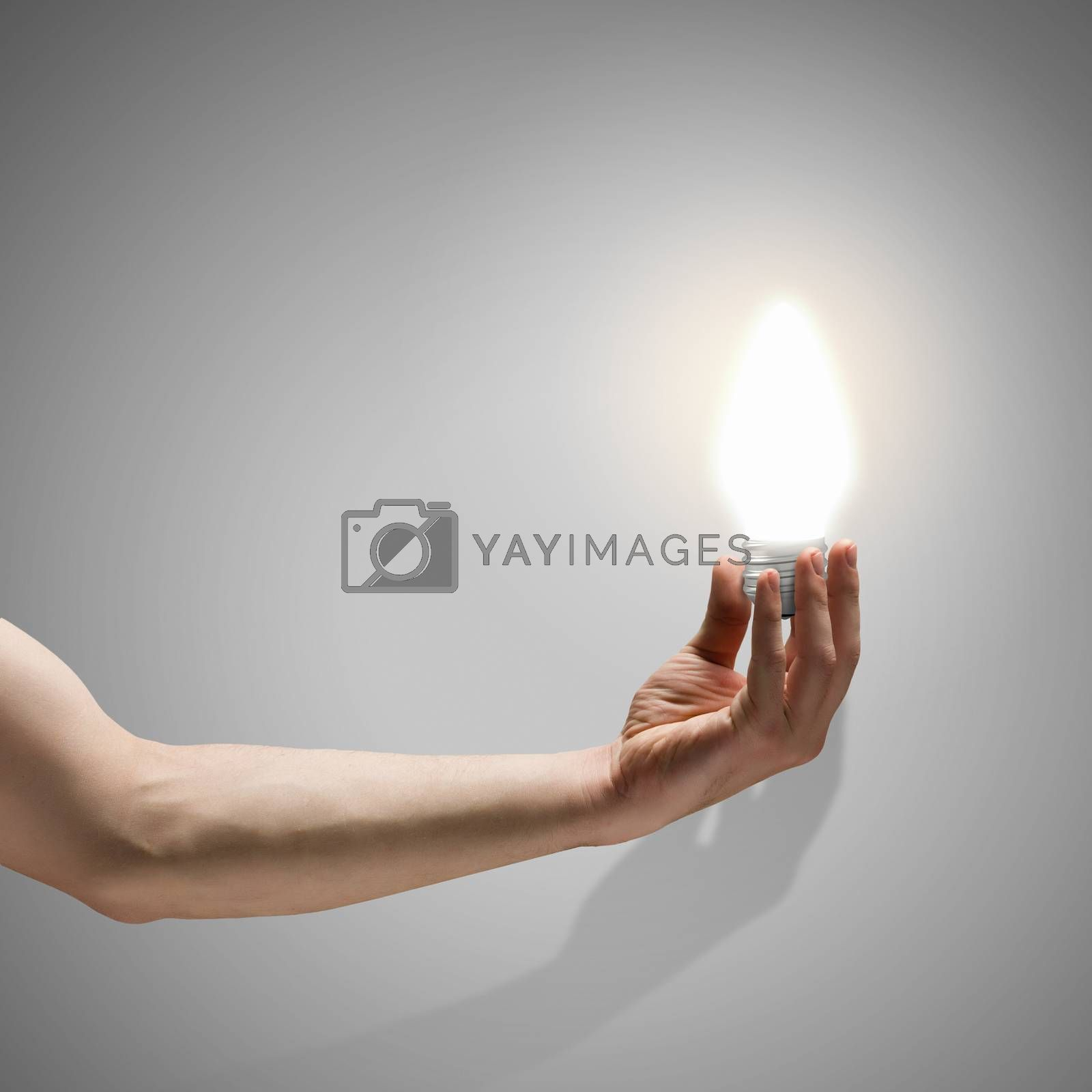 Close up image of human hand holding electrical bulb
