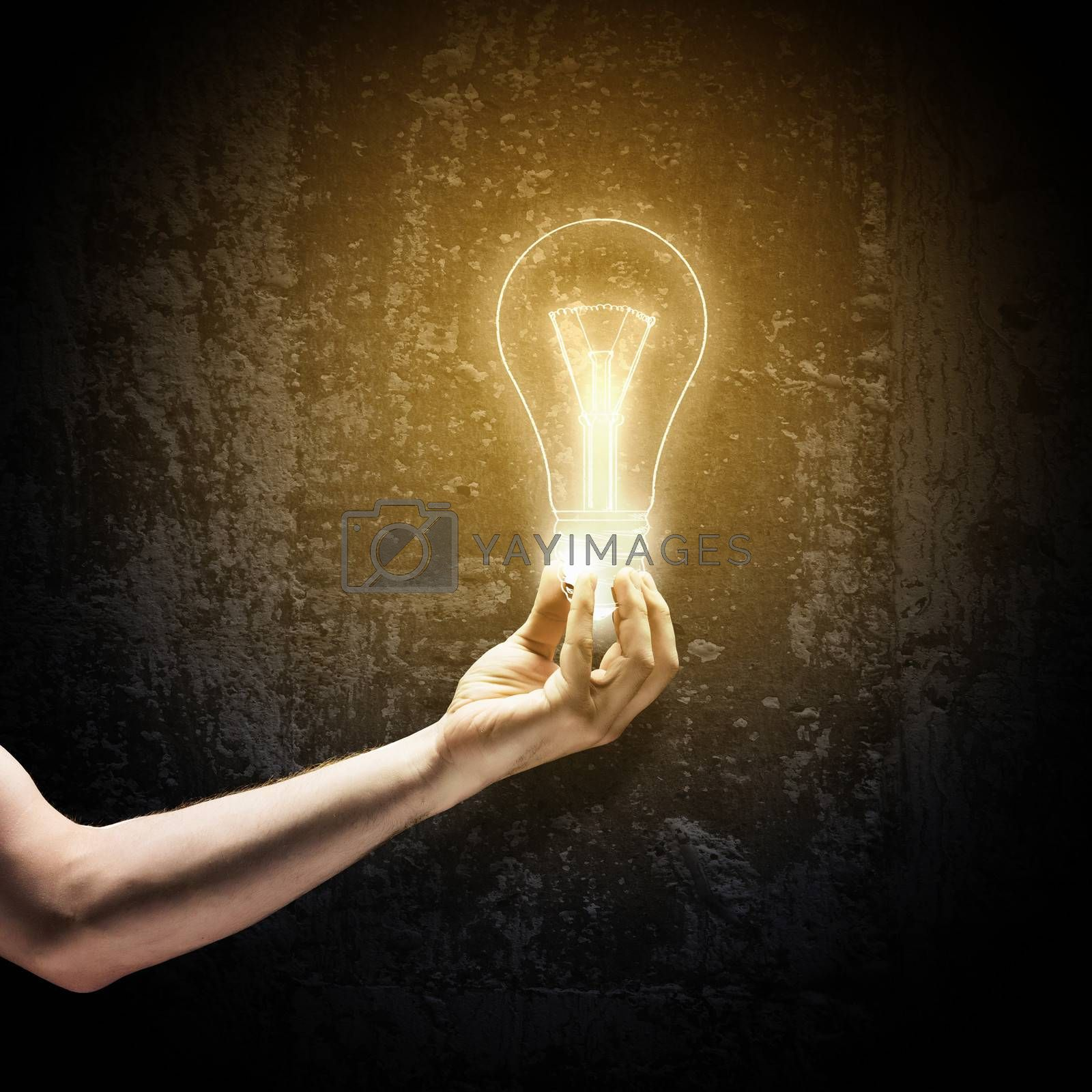Close up image of human hand holding electrical bulb in darkness