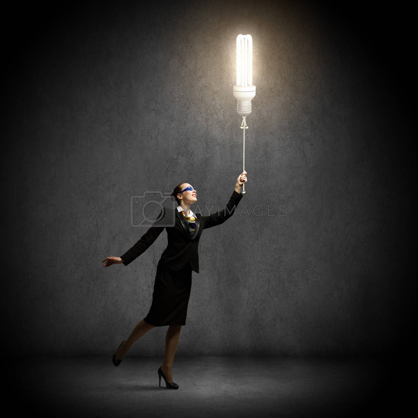 Image of businesswoman holding bulb balloon. idea concept