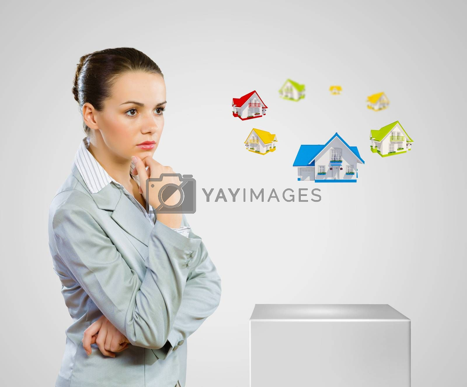 Image of young woman in suit looking at house model. Construction