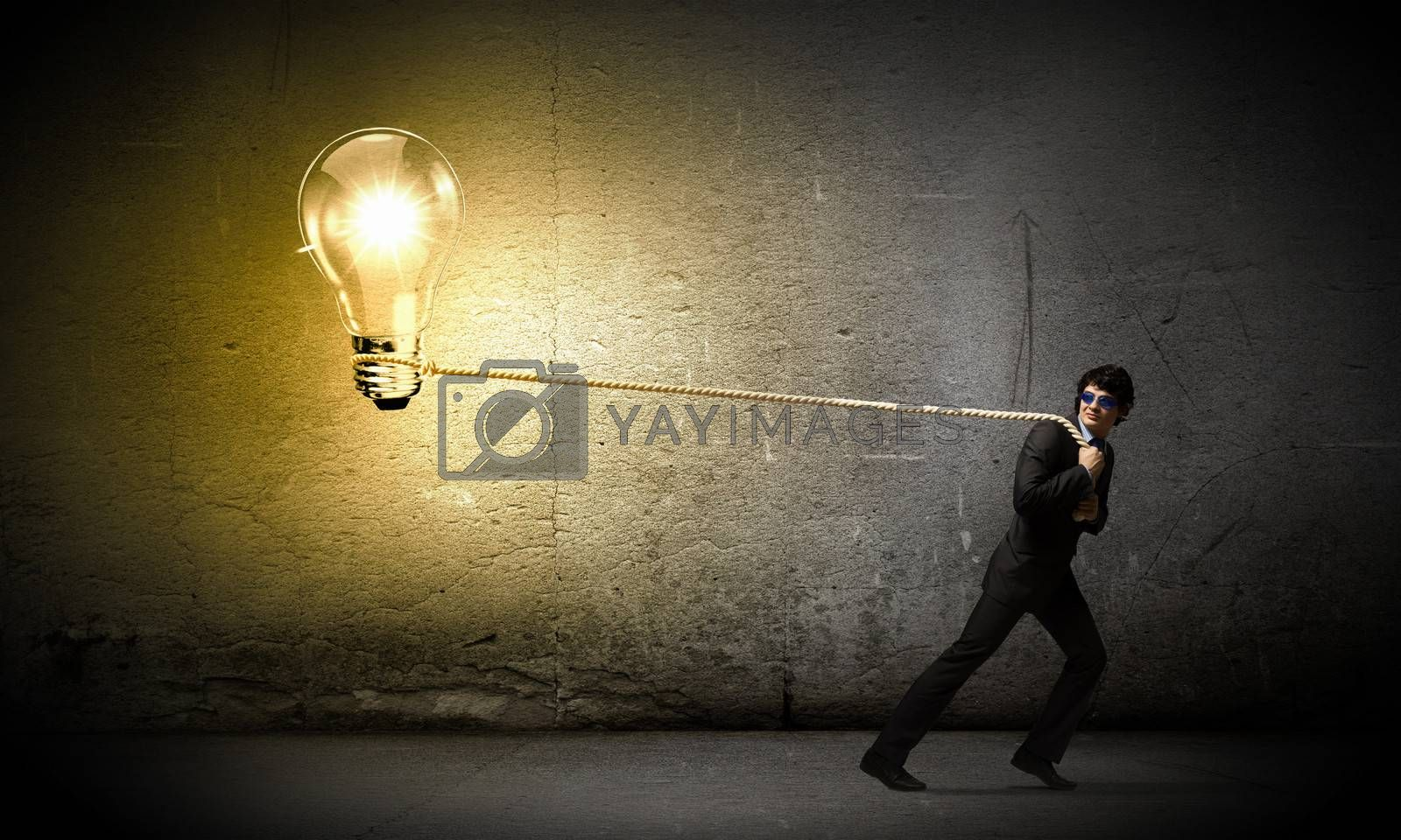 Image of young businessman pulling bulb with rope