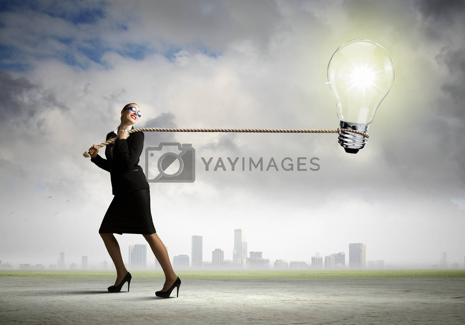 Image of businesswoman pulling electrical bulb with rope