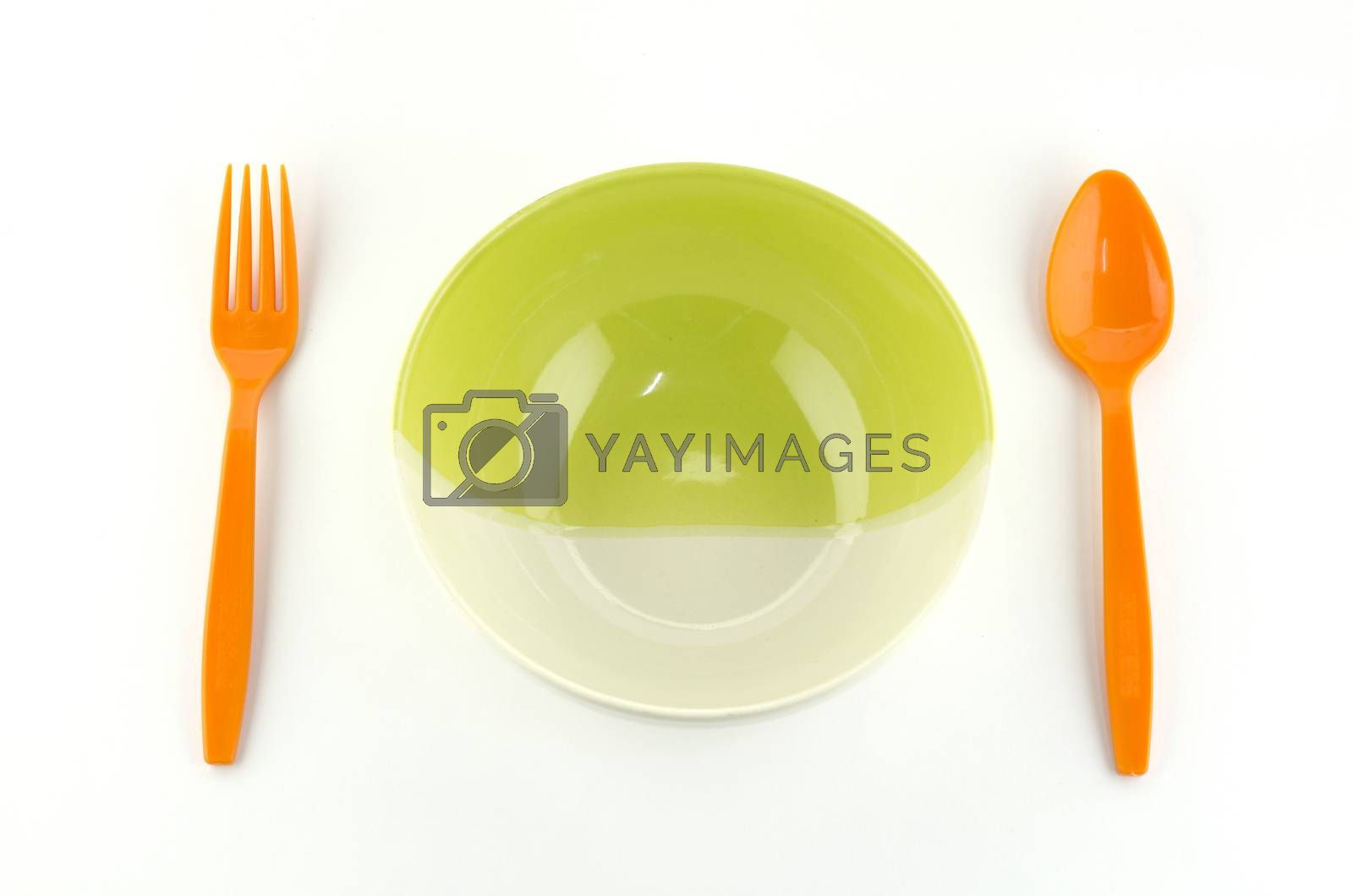 green white bowl with orange spoon and fork isolated on white background