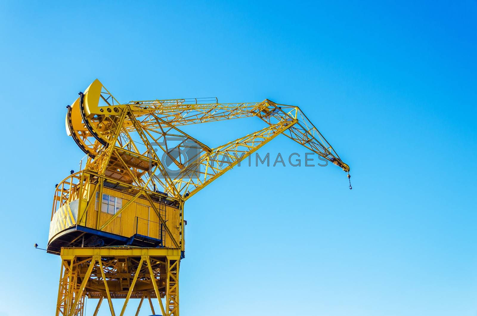 Old yellow crane in Buenos Aires with a beautiful blue sky