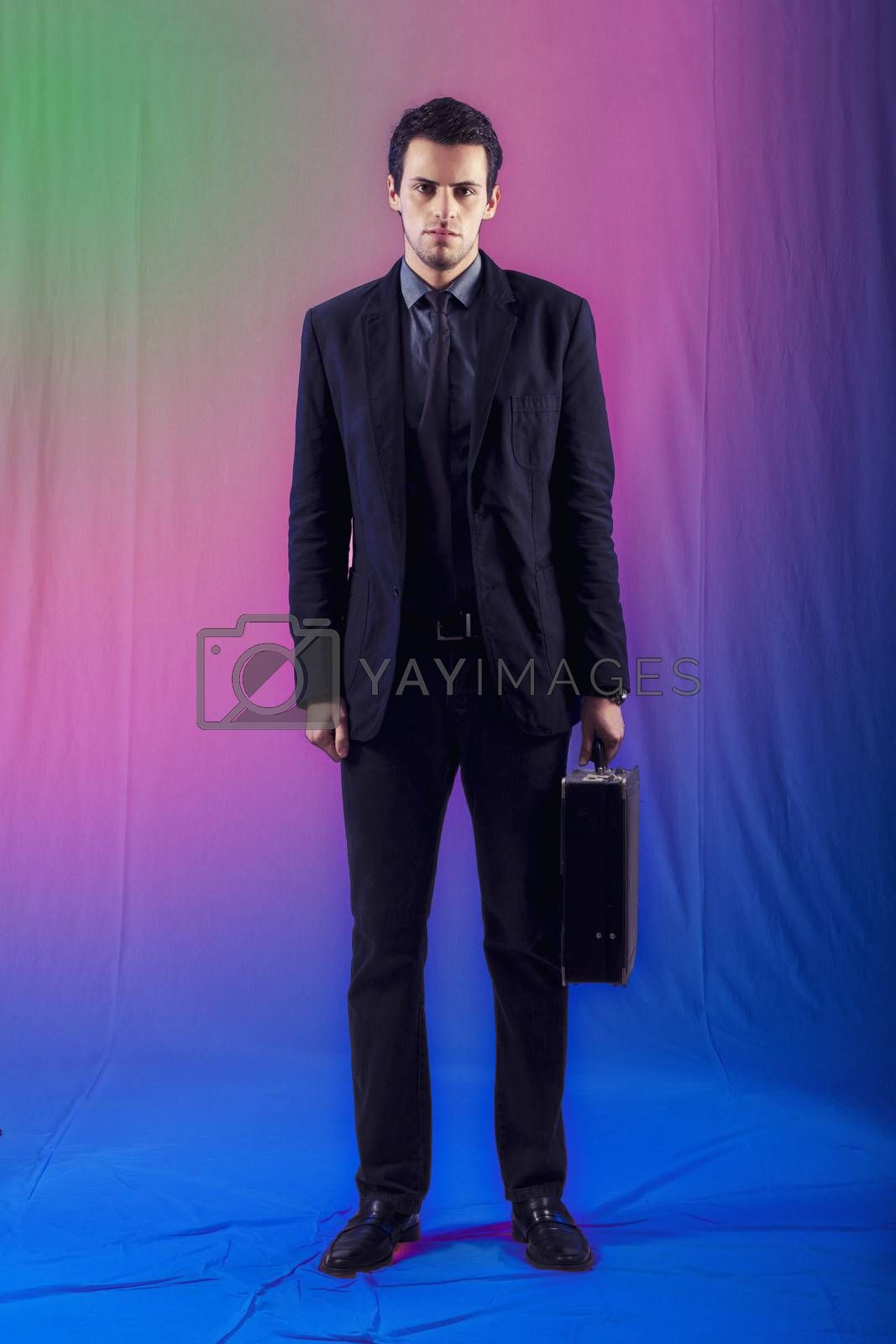 View of a young business man standing against a colorful  background.