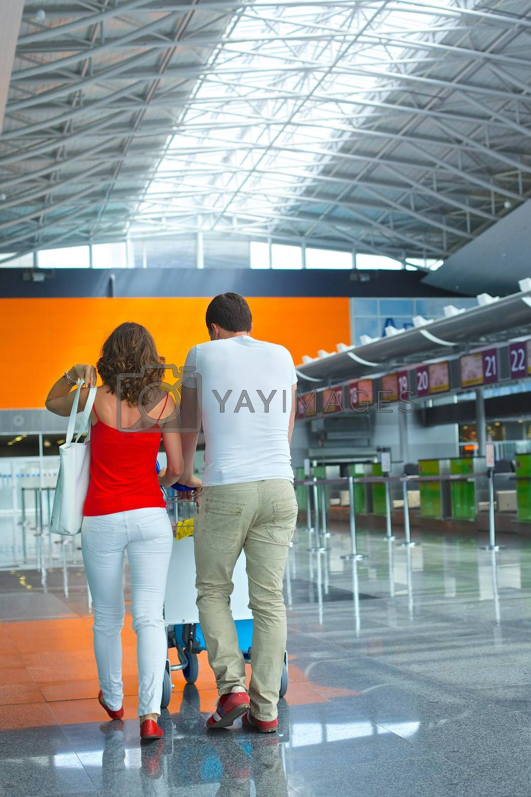 Back view of standing traveling couple with suitcases in airport