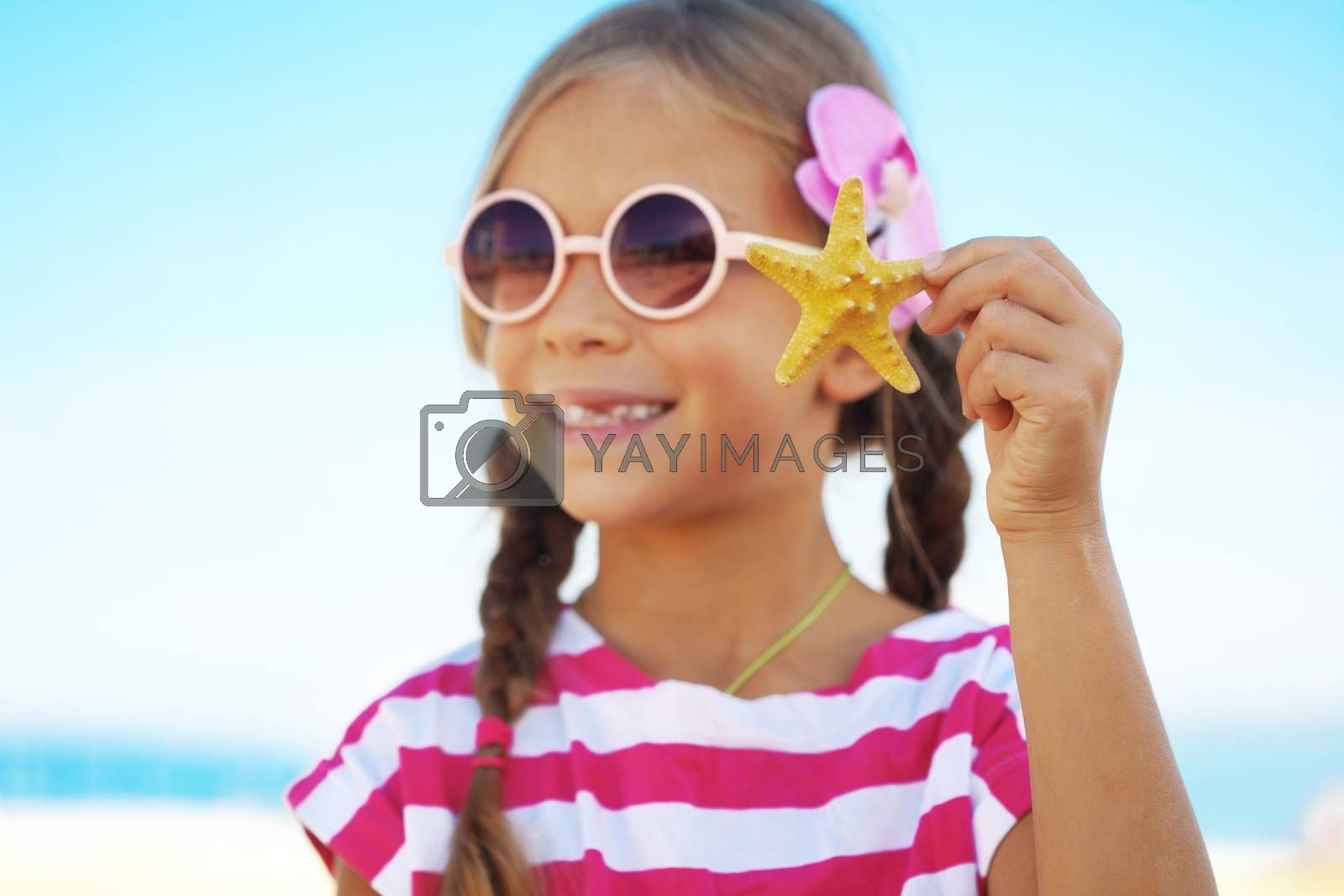 Child holding seashell at the summer beach