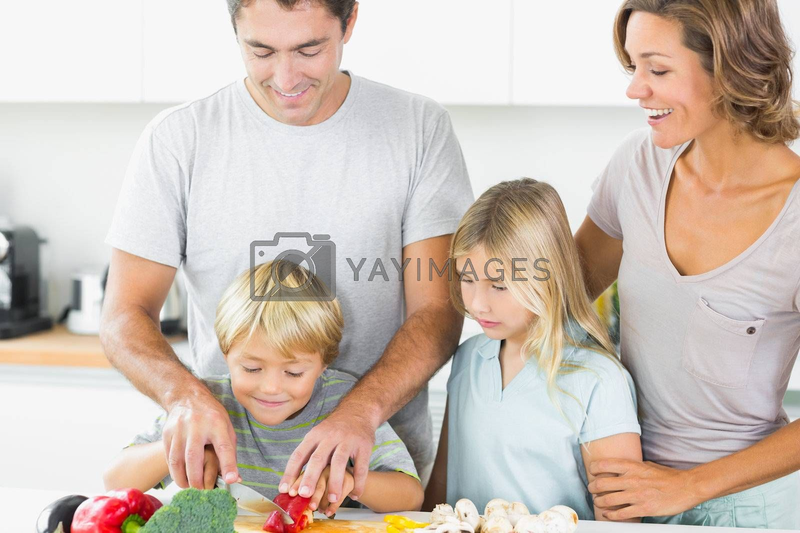 Mother and daughter watching father and son slicing vegetables by Wavebreakmedia