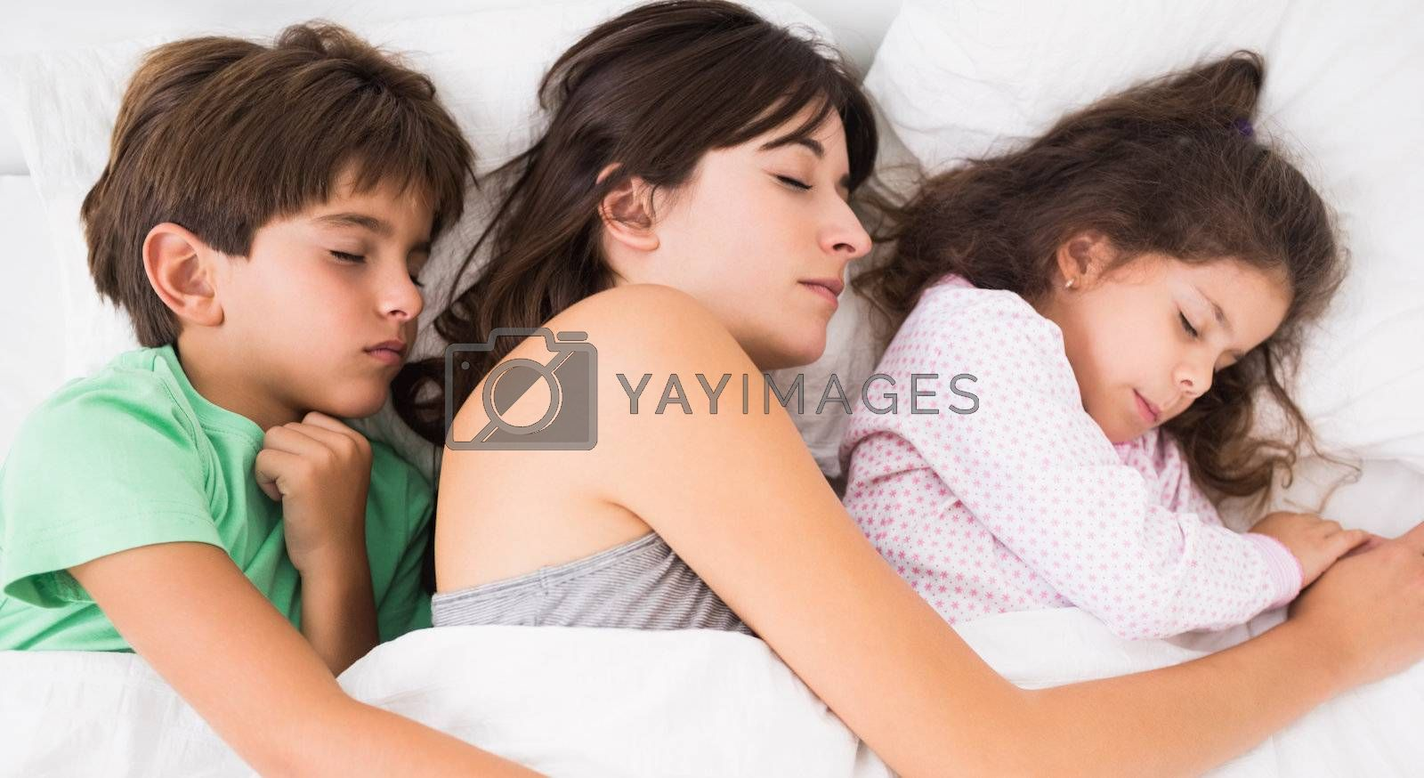 Mother sleeping with son and daughter cuddled up