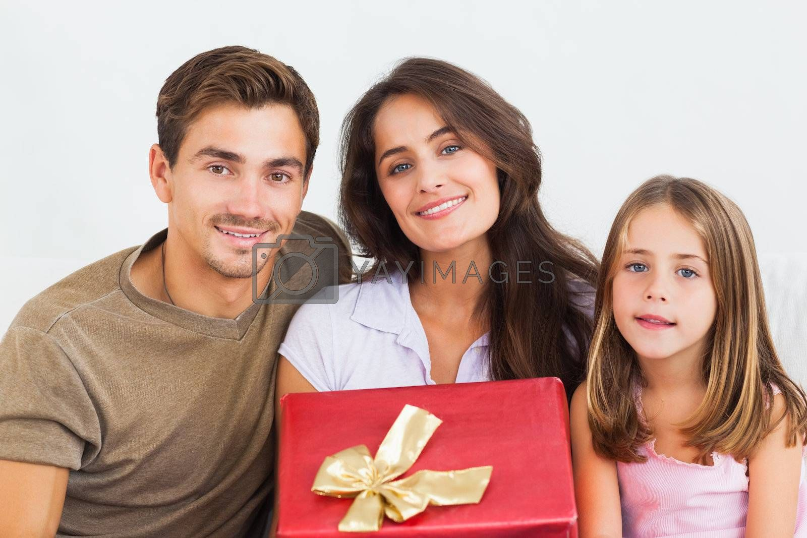 Father and his daughter offering a gift to her mother in the living room