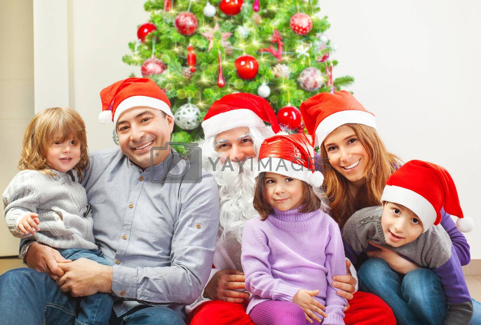 Large family and Santa Claus sitting near Christmas tree at home, wearing red festive hat, winter holidays, New Year celebration