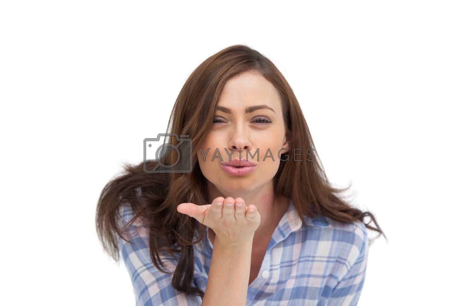 Cute woman blowing a kiss to the camera on white background